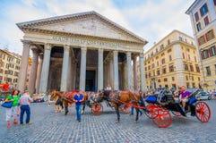 ROME ITALIEN - JUNI 13, 2015: Panteon av Agrippa i mitten av Rome, hästar som drar den röda vagnen utanför i Arkivbild