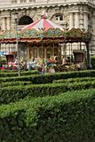 Ancient carousel in a public park. In the foreground hedges with royalty free stock image