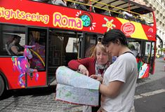 Rome, Italy - APRIl 7, 2017 : Two tourists looking map of Rome. In the background tourist bus with passengers on street in Rome, Italy Stock Photography