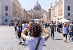 ROME, ITALY - APRIL 27, 2019: Young woman photographs the Saint Peter`s Basilica, Rome, Italy. royalty free stock image