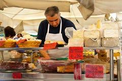 ROME, ITALY - APRILE, 6: Seller of cheese and prosciutto on the market Campo dei Fiori, Aprile 6, 2013 Stock Photos