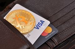 Rome, Italy, August 18, 2018. Bitcoin gold coin and debit cards. Visa and MasterCard in a wallet leather stock photo