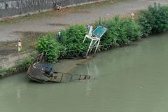 Wild bank of the river Tiber in Rome, Italy. Rome, Italy - August 3, 2018: Shipwreck and waste along the bank of the river Tiber royalty free stock image