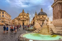 Tourists in Piazza del Popolo watching the churches and the Fontana dell`Obelisco royalty free stock images