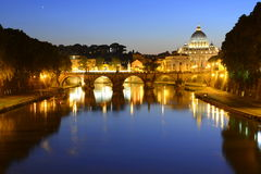 Rome, Italy, Basilica di San Pietro and Sant Angelo bridge at night. Basilica of San Pietro at night overlooking the Tevere river and surrounding historical stock images
