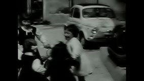 Children playing in the yard. Rome, Italy - Circa 1960 - children playing in the courtyard of a building where cars of the time are parked. Shooting carried out stock video