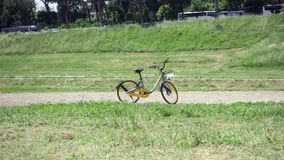 ROME, ITALY - CIRCA May 2018: Stationless oBike bicycle standing on Circus Maximus in Rome, Italy. ROME, ITALY - CIRCA May 2018: Yellow oBike bicycle standing on stock video footage