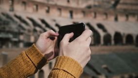 ROME, ITALY-11.02.2017 Close-up view of female hands taking photos of ruins on smartphone. Woman standing in Colosseum. stock video footage