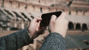 ROME, ITALY-11.02.2017 Close-up view of male hands talking photos of ruins on smartphone. Young man in Colosseum. stock footage