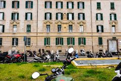 Many scooters parked in front of an old building in Rome Stock Photo