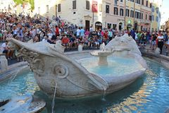 Rome, Italy, Europe - August 18, 2015: Crowds of tourists gather around the Spanish Steps and a boat-shaped fountain on Piazza di royalty free stock image