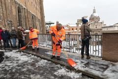 Snow covers the streets of Rome, Italy. Staff member clears the. Rome, Italy - February 26, 2018: An exceptional weather event causes a cold and cold air across royalty free stock image