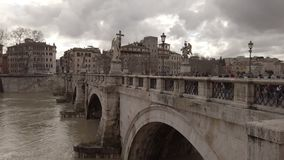 Saint Angel Bridge profile view in a cloudy winter day with many tourists walk. Rome, Italy - February 03, 2019: Profile view of Saint` Angel bridge in a cloudy stock video footage