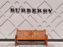 Burberry logo above an empty bench Royalty Free Stock Image