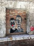 Graffiti with clowns faces on the brick wall. Rome, Italy - July 16, 2017: graffiti with clowns faces on the brick wall in Rome, Italy Royalty Free Stock Photo