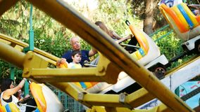 People and kids having fun at baby rollercoaster stock video