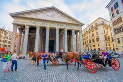 ROME, ITALY - JUNE 13, 2015: Pantheon of Agrippa in the center of Rome, horses pulling the red wagon outside in the Stock Photography