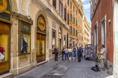 ROME, ITALY - JUNE 17, 2014: People walking along narrow cobblestone streets with shops,trade with souvenirs. A street musician stock image