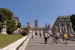 Tourists on Michelangelo stairs to Piazza del Campidoglio on the top of Capitoline Hill stock image