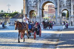 Two carriages transport tourists along Via Dei Fori Imperiali near the famous Arch of Constantine. Rome, Italy - June 30, 2018: Two carriages transport tourists Stock Photography