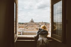 Woman watches from window on the Papal Basilica of St. Peter. Rome, Italy - June 22, 2018: Woman watches from window on the Papal Basilica of St. Peter (St royalty free stock images