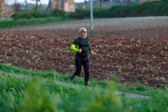 Man runs training in the green of the public park. In the background freshly plowed agricultural land. Rome, Italy - March 29, 2019: A man runs training in the stock photos