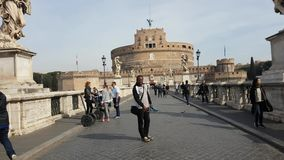 Tourists around Saint Angel Castle and bridge over the Tiber river in Rome stock footage