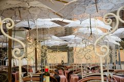 Rome, Italy. November 2017. Tables laid and decorated with delicious embroidered umbrellas. Exterior of a restaurant furnished with embroidered white tables and Stock Images