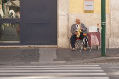 Rome, Italy, October 9, 2011: Elderly man plays saxophone at the entrance to the bank royalty free stock photos