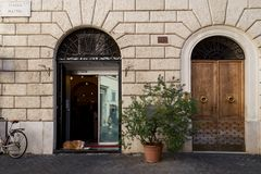 Rome, Italy - October 1, 2019: Lovely dog lying at the entrance of the shop.
