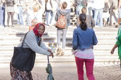 Rome, Italy, October 9, 2011: Older woman asking for alms at the entrance to a Catholic church stock photo