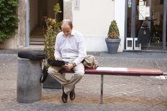 Rome, Italy, October 14, 2011: Young man sitting on a street bench with a laptop royalty free stock photography