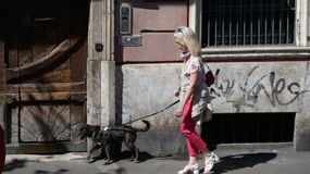 ROME ITALY - 06.24.2020: reportage photo of a woman with a dog walking on the sidewalk
