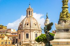 Rome, Italy - September 12, 2017: Bronze angel touches the dome of the Church. Bronze angel touches the dome of the Church. Bronze statue of young woman with royalty free stock image