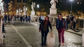 Tourists and Romans walking along Sant`Angelo Bridge on a late summer evening stock video footage