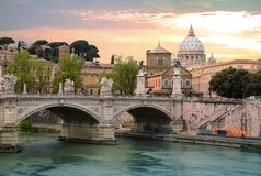 ROME, ITALY. St Peter`s basilica in Vatican, river Tiber view and Roma`n bridge. At sunset royalty free stock photo