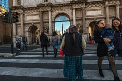 11/09/2018 - Rome, Italy: Sunday afternoon in the city center,people crossing road at piazzale flaminio. Center figure is. A gyspy beggar royalty free stock image