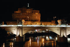 Rome by Night. Night view of Saint Angel Castle in Rome (background) in early August with a bridge over Tiber river Stock Image