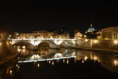 Rome by night. A night view of Rome, Italy, with the Tiber river, the Vittorio Emanuele II bridge and the Saint Peter Basilica Stock Photos