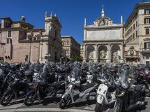Rome is ranked among the cities with the most registered scooter. S in the world. Various scooters are parked in front of a historic building in Rome Royalty Free Stock Photo