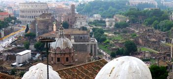 Rome ruins panorama. Ruins of ancient Rome at Forum Romanum with Colosseum in background royalty free stock photo