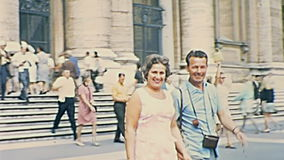Rome Saint Peter tourists. ROME, ITALY - CIRCA 1967: tourists at Saint Peter basilica church. Panorama of San Pietro Italian square with cars and bus of Roma stock footage