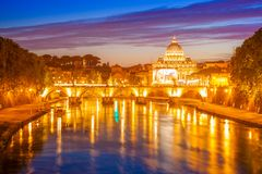 Rome by night. Rome skyline at night with San Pietro basilica or Saint Peter cathedral with Sant`Angelo bridge reflected on Tevere river illuminated by city Stock Image