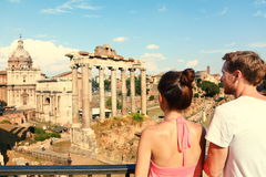 Rome tourists looking at Roman Forum landmark. In Rome. Couple sightseeing on travel vacation in Rome, Italy. Happy tourist couple, men and women traveling on royalty free stock photo