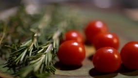 Romero fresco y tomates rojos jugosos sabrosos que mienten en el primer del tablero de la cocina La cámara se mueve de izquierda  almacen de metraje de vídeo