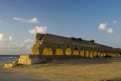 Romersk ålderaquaeductus i Caesarea i solnedgång Arkivfoto