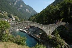 Romersk bro över floden på den Verzasca dalen Arkivfoto