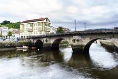 Romersk bro över Ria de Betanzos med en stark ström och Royaltyfria Foton