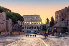 Romersk gata på gryning med en sikt av Colosseumen, Rome, Italien arkivfoton