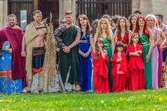 Romersk gladiator i striddräkt och en grupp av unga romerska flickor royaltyfri foto